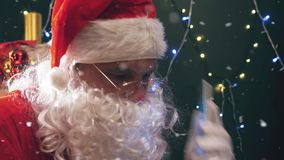 Santa buying gifts use mobile phone. Santa Claus using a mobile phone at Christmas time. Santa typing message or sms to Elf or Dwarf. Cristmas gift or present stock video footage