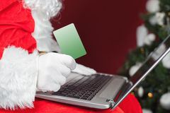 Santa buying by plastic card Christmas gift in Internet Royalty Free Stock Photography