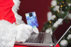 Santa buying by plastic card Christmas gift in Internet Royalty Free Stock Photo
