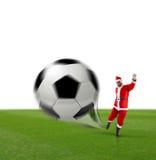 Santa Calus som sparkar en fotbollboll Royaltyfria Bilder