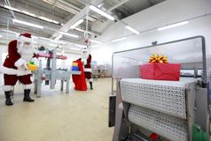 Santa Caluses in the christams gifts factory at assembly line Royalty Free Stock Photos