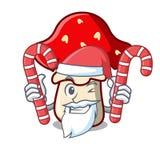 Santa with candy amanita mushroom mascot cartoon Stock Photos