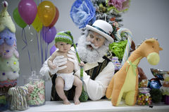 Santa in candy shop with baby Stock Images