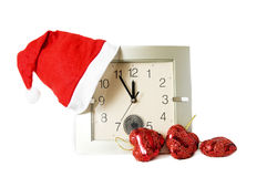 Santa cap on clock and some Christmas decoration. Over white royalty free stock image