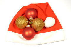 Santa cap and glass balls. Christmas decoration on Santa Claus cap isolated over white Stock Photography