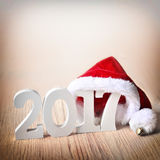 Santa cap on rustic wooden background with figures 2017 Stock Photos