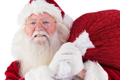 Santa carries his red bag and smiles Royalty Free Stock Photo