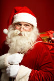 Santa carrying sack with gifts Stock Image