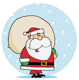 Santa carrying a toy sack in the snow Royalty Free Stock Photos