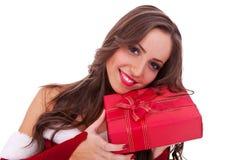 Santa che abbraccia un piccolo contenitore di regalo Immagine Stock