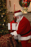 Santa che dispone un regalo fotografie stock libere da diritti