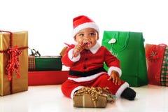 Santa che fa la spia una canna di caramella Immagine Stock