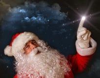Santa che indica con l'indicatore luminoso magico il cielo fotografie stock libere da diritti