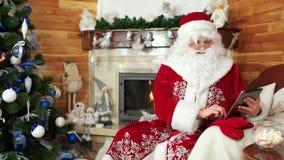 Santa che per mezzo del computer della compressa, san Nicolas che si siede nella sedia con l'apparecchio elettronico, Internet pr stock footage
