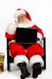 Santa che per mezzo del computer portatile fotografia stock libera da diritti