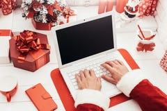 Santa che per mezzo di un computer portatile Fotografia Stock Libera da Diritti