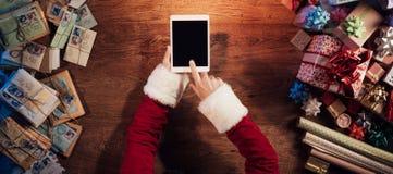 Santa che per mezzo di una compressa digitale Immagine Stock