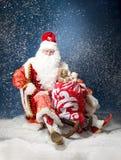 Santa che pilota la sua slitta contro la neve Immagine Stock