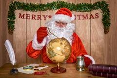 Santa che progetta il suo itinerario di consegna. Fotografia Stock