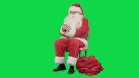 Santa che ride fragorosamente come parla sulla sua cellula stock footage