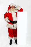 Santa che si appoggia sulla bandiera fotografia stock