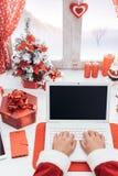 Santa che si collega con un computer portatile Immagini Stock