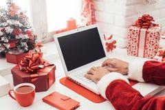 Santa che si collega con un computer portatile Immagine Stock