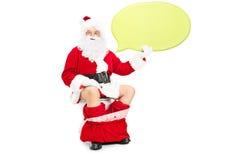 Santa che si siede sulla toilette e che tiene fumetto Immagine Stock