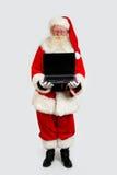 Santa che tiene un computer portatile immagini stock