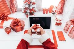 Santa che tiene un contenitore di regalo Fotografie Stock