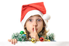 Santa child girl finger over lips quiet sign Stock Photos
