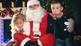 Santa and children around the decorated Christmas tree. Wishes stock video