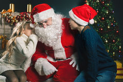 Santa and children around the decorated Christmas tree. Wishes list Royalty Free Stock Photos