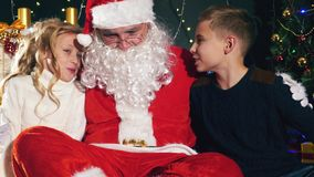 Santa and children around the decorated Christmas tree. Wishes list stock video footage