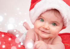 Santa Christmas Baby with Magic Sparkles. A baby is smiling with a santa hat and sparkles representing christmas magic. Use it for a holiday theme royalty free stock photo