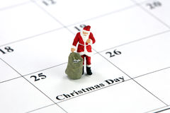 Santa on Christmas calendar. Miniature Santa Claus standing on a calendar with Christmas Day printed on it. Christmas concept Royalty Free Stock Image