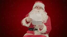 Santa with Christmas letter or wish list on red background with snow. Professional shot on BMCC RAW with high dynamic range. You can use it e.g in your Stock Image