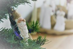 Santa Christmas Ornament Nativity Background. Christmas Santa ornament with nativity blurred in background.  Represents the current focus of Christmas Stock Image