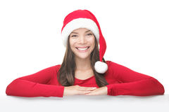 Santa Christmas woman leaning on sign billboard. Christmas woman smiling showing empty blank sign board. Asian Chinese / white Caucasian young female model in Royalty Free Stock Photo