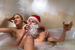 Santa with cigar and his girlfriend. Royalty Free Stock Photo
