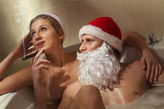 Santa with cigar and his girlfriend. Royalty Free Stock Image