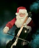 Santa Cklaus, die Cello über dunklem Hintergrund spielt Stockbilder