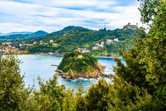 Santa Clara Island in San Sebastian, Biscay Bay, Basque Country, Spain. San Sebastian, Basque Country, Spain: Santa Clara Island located between the mountains of stock images