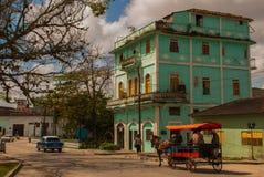 SANTA CLARA, KUBA: Zwykła ulica w mieście Zielony kondygnacja budynek przewóz przez konia Końska fura odtransportowywać ludzi fotografia royalty free