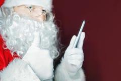Santa Claus à l'aide d'un téléphone portable au temps de Noël Photos stock