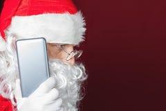 Santa Claus à l'aide d'un téléphone portable au temps de Noël Photo libre de droits