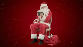 Santa Claus à l'aide de la tablette pour surfer l'Internet et pour communiquer dans le media social avec des enfants sur le fond  photo libre de droits