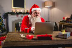Santa Claus à l'aide de l'ordinateur portable sur la table Photos libres de droits