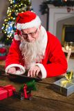 Santa Claus à l'aide du comprimé numérique sur la table Image libre de droits
