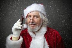 Santa Claus à l'aide du smartphone - appelant le téléphone ou textotant un message Photos libres de droits